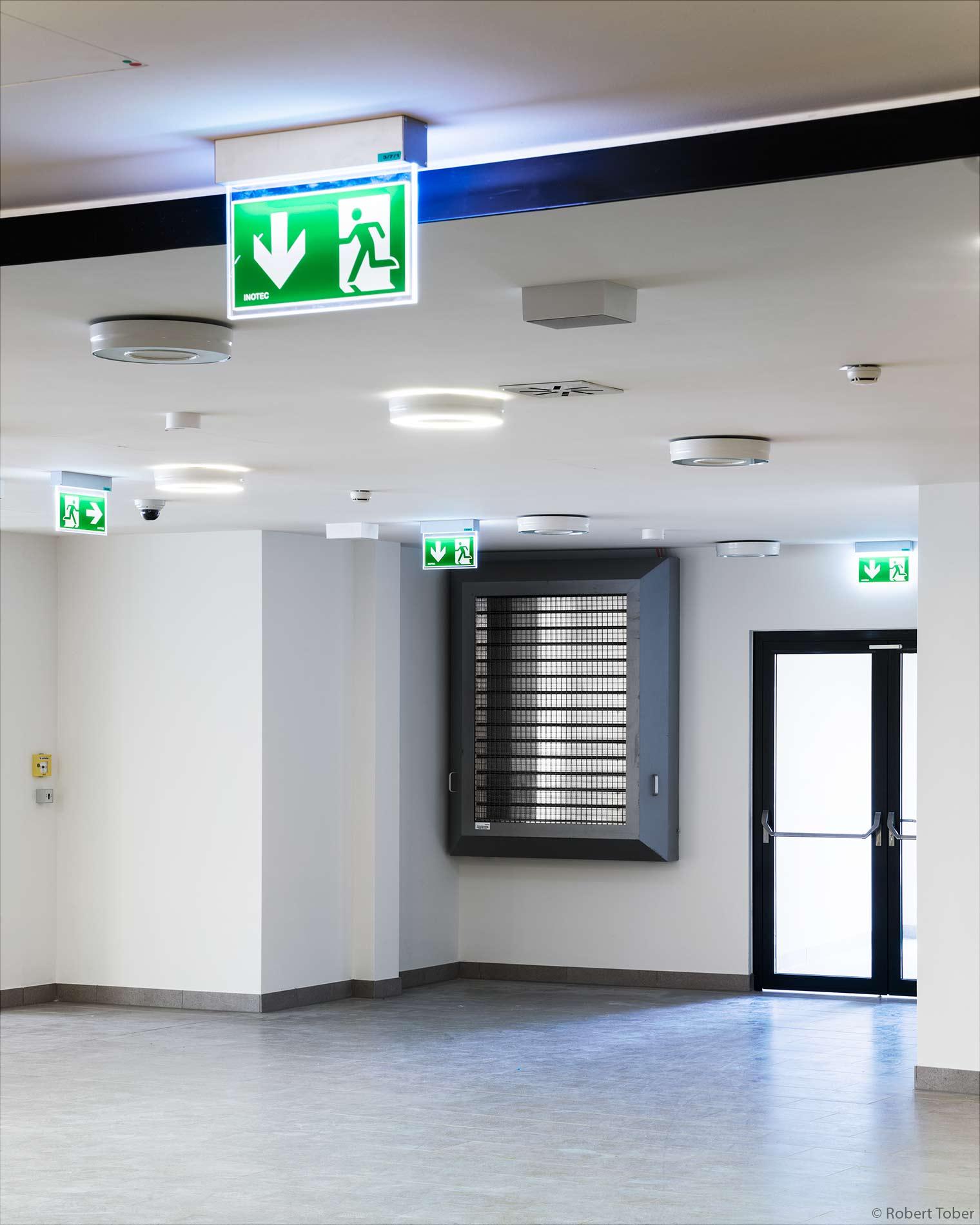 Landesklinikum Mistelbach · Fluchtwegkennzeichnung, Paniktürverschluss mit horizontaler Betätigungsstange nach DIN EN 1125, Brandrauch-Abzugsklappen / Entlüftungsklappen · © Robert Tober Architekturfotograf